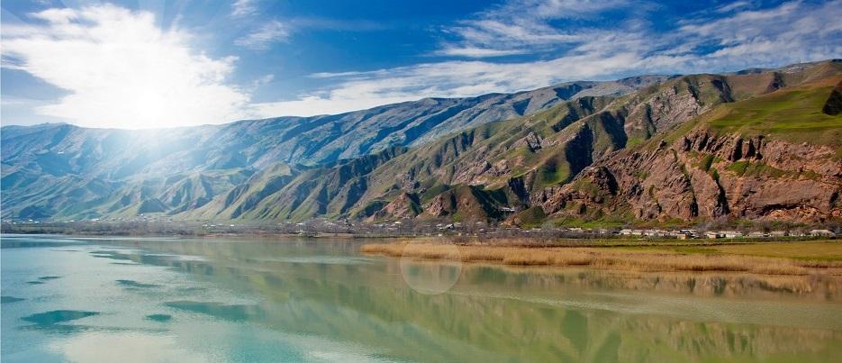 Sous le soleil des montagnes et un lac
